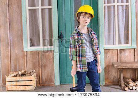 portrait of pensive boy in helmet with hammer on porch looking away