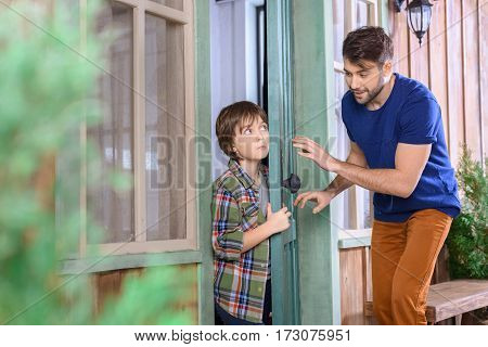 side view of man and boy playing hide and seek at home