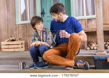 man and boy with cups of tea have conversation while sitting on porch