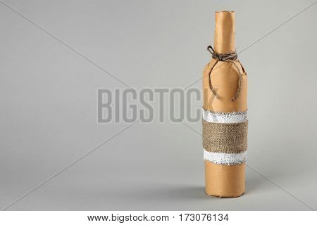 St. Valentine's Day concept. Wine bottle in gift wrap on light background