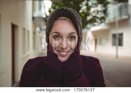 Portrait of beautiful woman posing with warm clothing in street