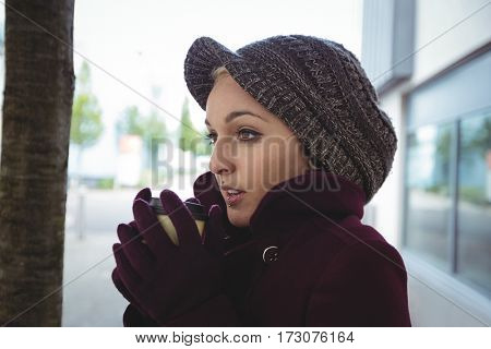 Woman shivering with cold in street