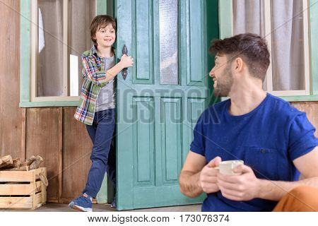 smiling man sitting on porch with tea cup and looking at boy behind
