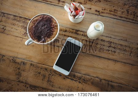 Coffee cup, mobile phone and milk bottle on a table at café
