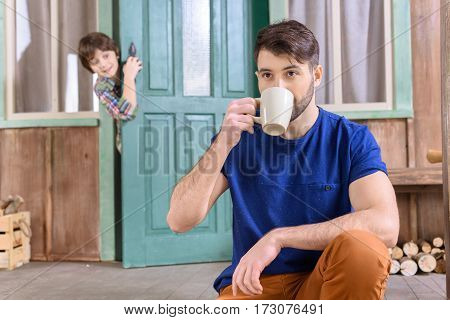 man drinking tea om porch and looking away while boy looking out from door behind