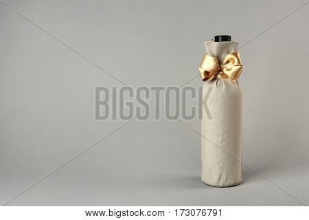 St. Valentine's Day concept. Wine bottle in gift linen pouch with satin ribbon on light background