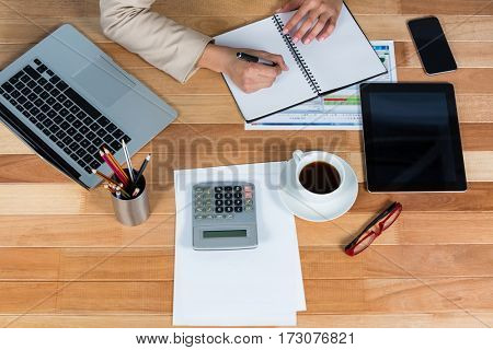 Businesswoman writing on a diary in office