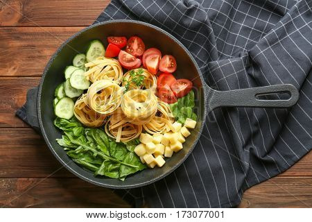 Pasta with vegetables and herbs in pan  on wooden table
