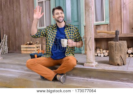 smiling man on porch waving to someone while holding tea cup and looking away