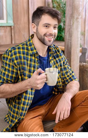 side view of smiling man sitting on porch with cup of tea and looking away