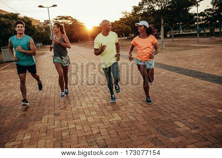 Young people running together at the park. Runners training outdoors in evening.