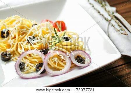 Plate of delicious pasta salad with olives and cheese