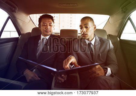 Businessmen explaining about report in the car