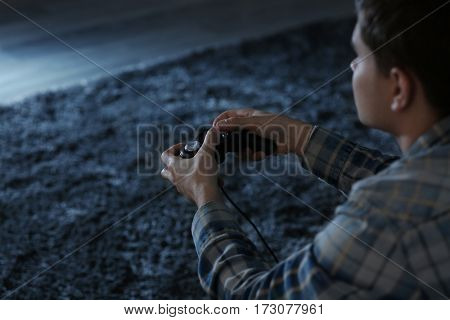 Teenager playing videogame at home late in evening