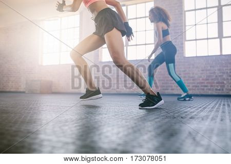 Low angle shot of females running in the gym. Legs of women exercising in healthclub.