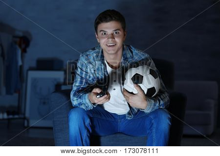 Teenager watching football match late in evening