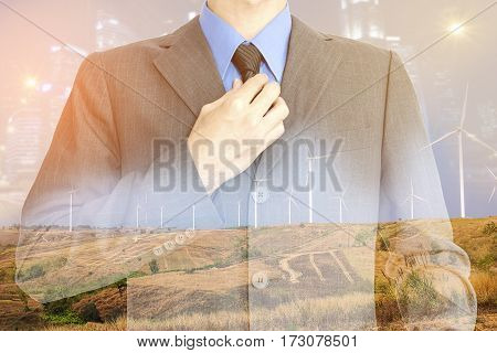 double exposure of businessman in suit with a blurred background of the night light city and wind turbine for electricity production.