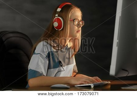 Pretty teenager playing computer game at home