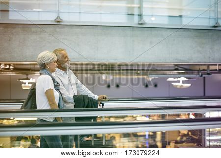 Lovely senior couple tourists on travelator