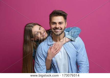 Cute young couple on color background