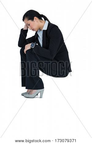 Depressed businesswoman sitting on steps against white background
