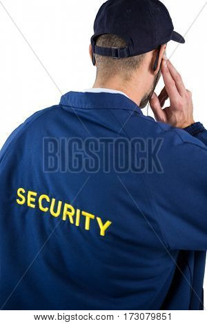 Rear view of security officer listening to earpiece against white background