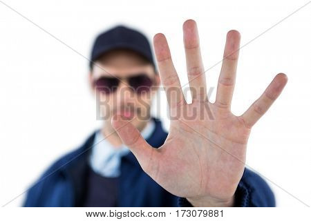 Confident security officer making stop gesture against white background