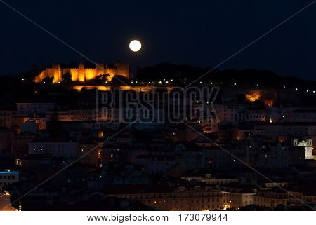The lisbon castle during a huge full moon, seen from the opposite viepoint at bairro alto
