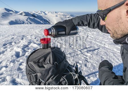 Hiker Pours Hot Tea From A Thermos In The Mountains.