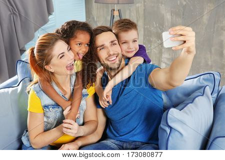 Happy interracial family making selfie on sofa