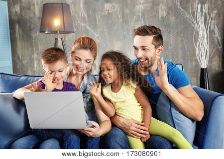 Happy interracial family with laptop on sofa