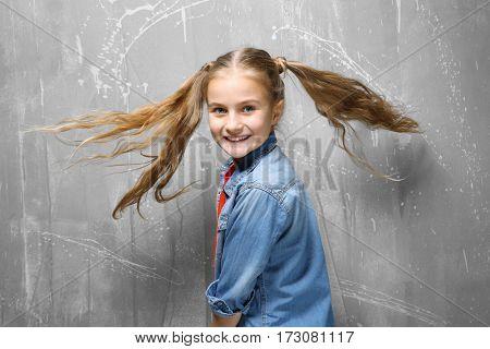 Emotional little girl on grey textured background
