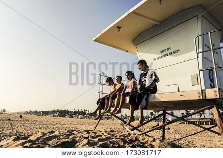 Huntington Beach California - 11 April 2009: Kids sitting on a lifeguard hut watching the ocean on a sunny afternoon