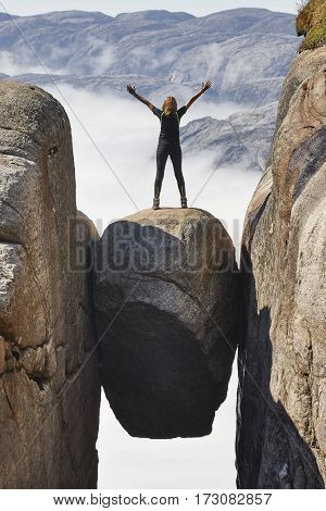 Norwegian fjord landscape. Woman hiker. Kjeragbolten landmark. Norway adventure tourism
