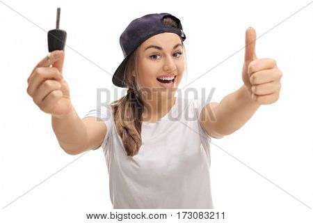 Overjoyed teenage girl holding a car key and making a thumb up sign isolated on white background