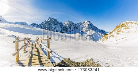 Bridge on the snowy trail in the italian alps Sulden, Solda with Ortler, Zebru, Grand Zebru in background. Val Venosta, South Tirol, Italy.