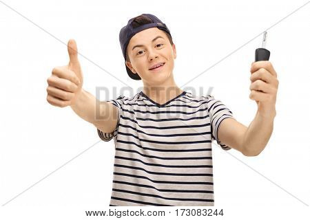 Joyful male teenager making a thumb up gesture and holding a car key isolated on white background
