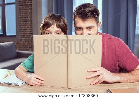 father and son looking out of book at home