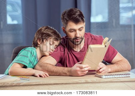 father reading book to sleeping son on shoulder
