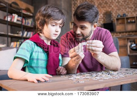 side view of father showing son how to playing with puzzles