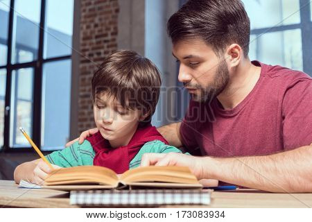 low angle view of father helping concentrated son with homework