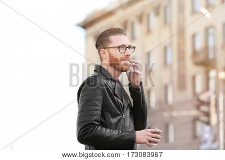 Young man with cup of coffee talking on phone outdoors