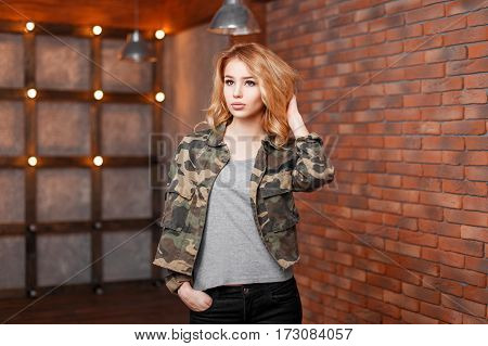 Beautiful Young Woman In A Stylish Jacket Near A Brick Wall And Lights