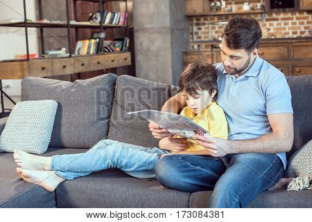 focused father and son reading newspaper together at home