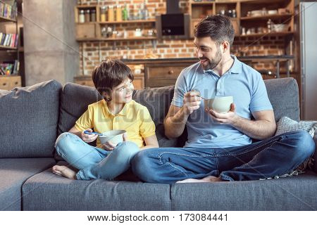 father and son sitting on couch together while eating breakfast