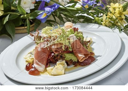 meat salad with ham cheese lettuce Dorblu grapes and olive oil served on a plate on a table with flowers