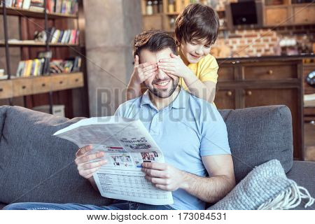 boy closing father's eyes while reading newspaper at home