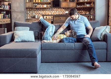 Happy father and son having fun together on sofa