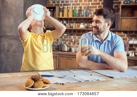 Smiling father with orange juice looking at son eating breakfast from bowl