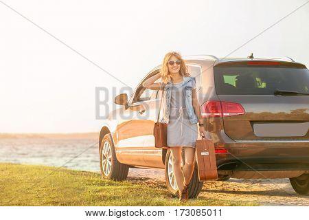 Beautiful young woman near car on river shore